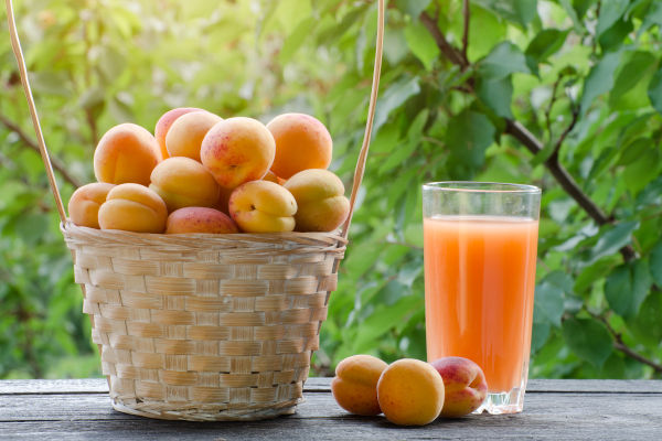 Apricots in a wicker basket and a glass of juice